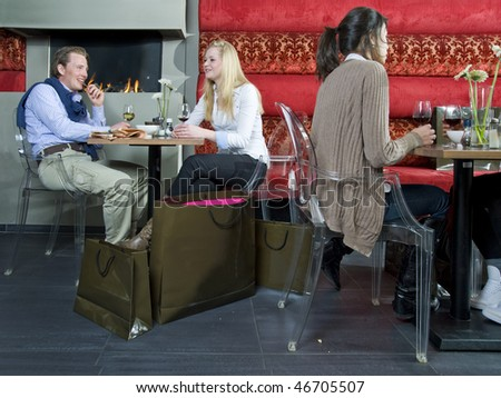 People having drinks after a day of shopping in a cafe - stock photo