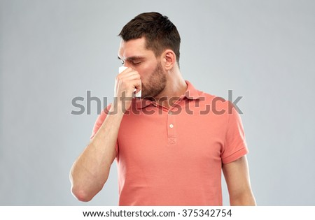 people, healthcare, rhinitis, cold and allergy concept - sick man with paper napkin blowing nose over gray background - stock photo