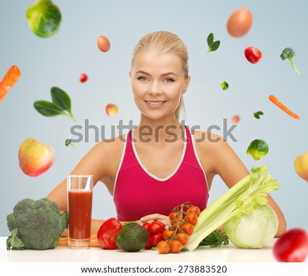 people, healthy eating, vegetarian and health care concept - happy woman with organic food and falling vegetables over gray background - stock photo