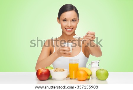 people, healthy food, diet and weight loss concept - happy beautiful woman with fruits eating yogurt for breakfast over green background - stock photo
