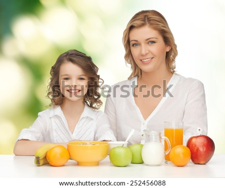 people, healthy lifestyle, family and food concept - happy mother and daughter eating healthy breakfast over green background - stock photo