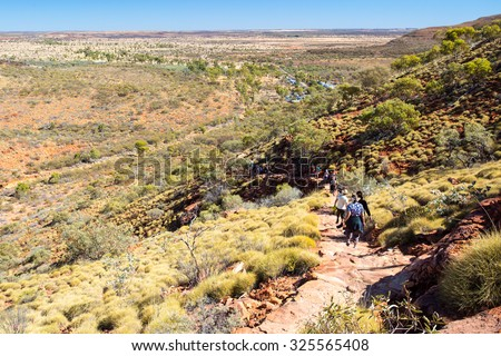 People hike down a cliff edge at Kings Canyon in Northern Territory, Australia - stock photo