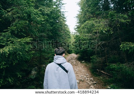 People hiker walking in the Misty mountain forest. Green pine forest landscape - stock photo