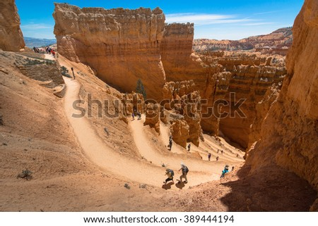 People, hikers, hiking on the trail into the canyon at Bryce Canyon National Park. This hiking trail was named Wall Street part of the hiking trail,  The hiking trail was named Navajo Loop  - stock photo