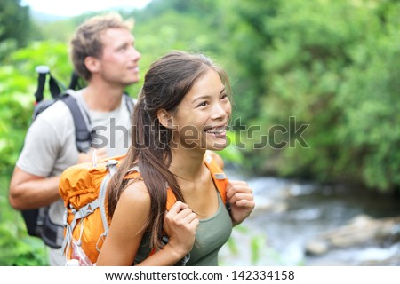 People hiking - happy hiker couple trekking as part of healthy lifestyle outdoors activity. Young multiracial couple walking in nature in Iao Valley State Park, Wailuku, Maui, Hawaii, USA. - stock photo