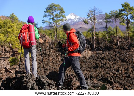 People hiking - healthy active lifestyle hikers. Hiker couple hiking in beautiful mountain nature landscape. Woman and man hikers walking during hike on volcano Teide, Tenerife, Canary Islands, Spain. - stock photo