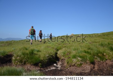 People hiking on path to the Ben Nevis summit - the highest mountain in the United Kingdom - stock photo