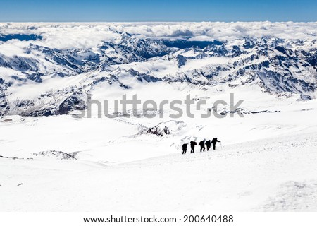 People hiking silhouette and climbing on snow in high mountain, Elbrus landscape in autumn or winter, Caucasus Mountains i Russia and Georgia. Mountain ridge over blue sunny sky - stock photo
