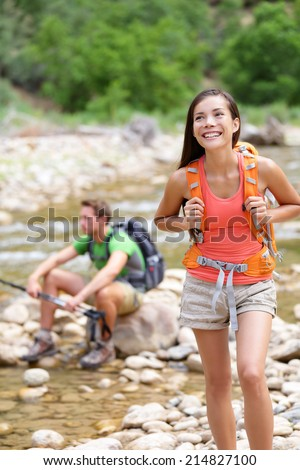 People hiking - woman hiker walking in Zion National Park, man in background. Hikers trekking by river water creek in forest enjoying view smiling happy. Young couple on trek hike in Utah, USA.