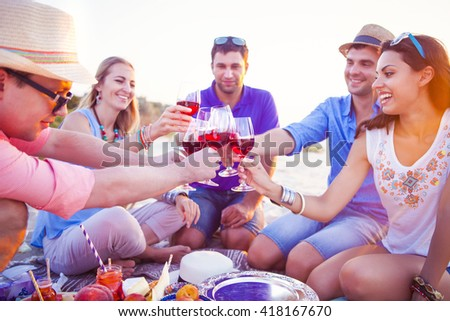 People holding glasses of red wine making a toast at the beach picnic - stock photo