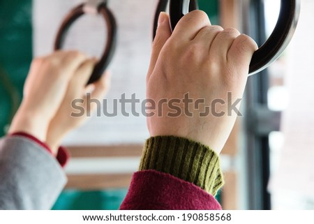 people holding onto a handle on a bus - stock photo
