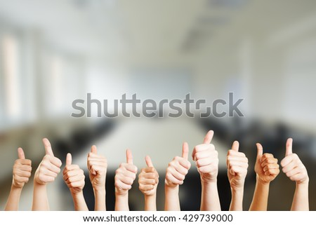 People holding thumbs up in a conference room at their office - stock photo