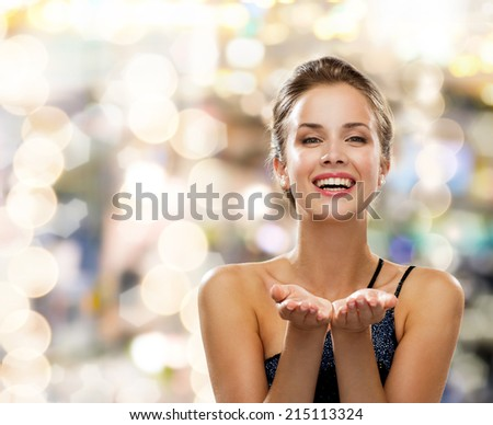 people, holidays, advertisement and luxury concept - laughing woman in evening dress holding something imaginary over lights background - stock photo