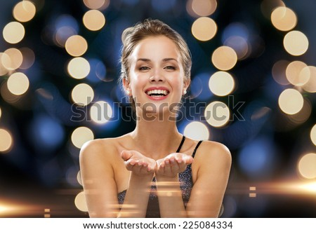 people, holidays, advertisement and luxury concept - laughing woman in evening dress holding something imaginary over night lights background - stock photo