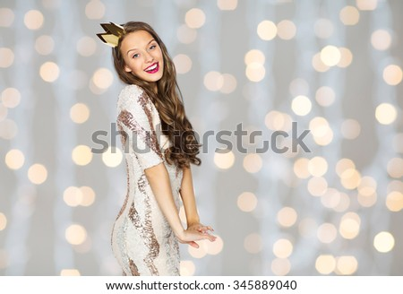 people, holidays and celebration concept - happy young woman or teen girl in party dress and princess crown over holidays lights background - stock photo