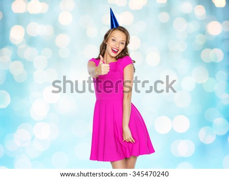 people, holidays and celebration concept - happy young woman or teen girl in pink dress and party cap over blue holidays lights background - stock photo
