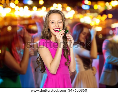 people, holidays and celebration concept - happy young woman or teen girl in pink dress blowing to party horn at night club over crowd and lights background - stock photo