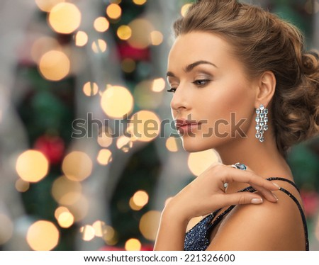 people, holidays and glamour concept - beautiful woman in evening dress wearing ring and earrings over christmas lights background - stock photo