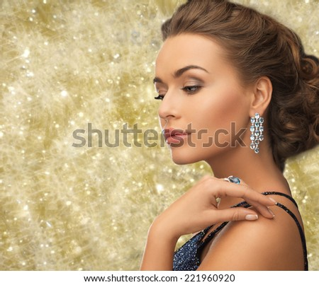 people, holidays and glamour concept - beautiful woman in evening dress wearing ring and earrings over yellow lights background - stock photo