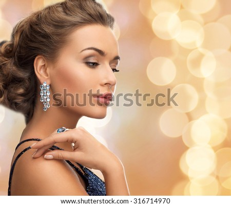 people, holidays and glamour concept - beautiful woman in evening dress wearing ring and earrings over beige lights background - stock photo