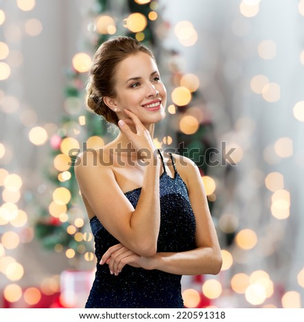 people, holidays, and glamour concept - smiling woman in evening dress showing earrings over christmas tree and lights background - stock photo