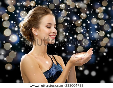 people, holidays and glamour concept - smiling woman with diamond over night lights and snow background