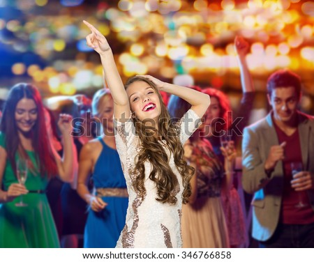 people, holidays and nightlife concept - happy young woman or teen girl in fancy dress with sequins and long wavy hair dancing at night club party over crowd and lights background - stock photo