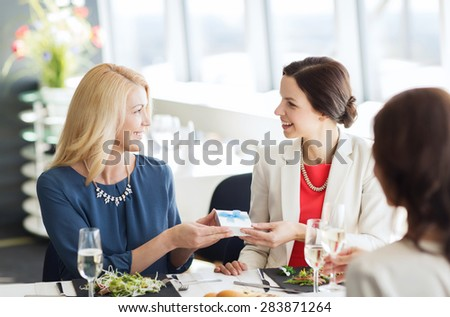 people, holidays, celebration and lifestyle concept - happy women giving birthday present at restaurant