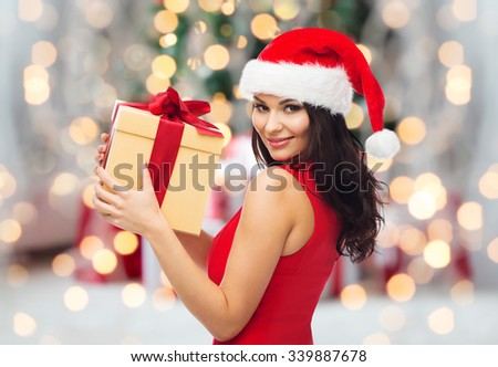 people, holidays, christmas and celebration concept - beautiful sexy woman in red dress and santa hat with gift box over christmas tree lights and presents background - stock photo