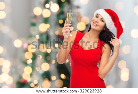 people, holidays, christmas and celebration concept - beautiful sexy woman in santa hat and red dress with champagne glass over lights background - stock photo