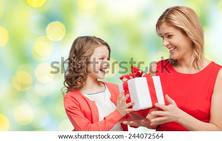 people, holidays, christmas and family concept - happy mother and daughter giving and receiving gift box over green lights background - stock photo
