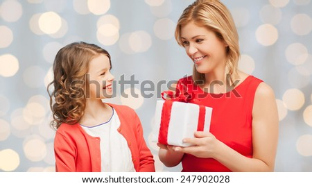 people, holidays, christmas and family concept - happy mother and daughter giving and receiving gift box over holiday lights background - stock photo