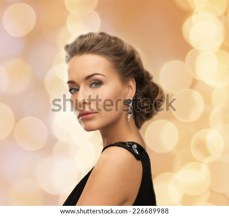people, holidays, christmas and glamour concept - beautiful woman in evening dress wearing earrings over beige lights background - stock photo