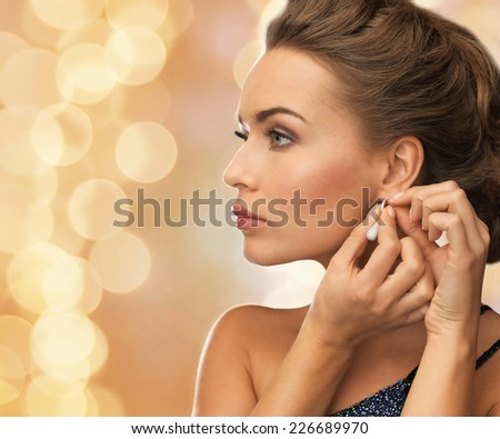 people, holidays, christmas and glamour concept - close up of beautiful woman wearing earrings over beige lights background - stock photo