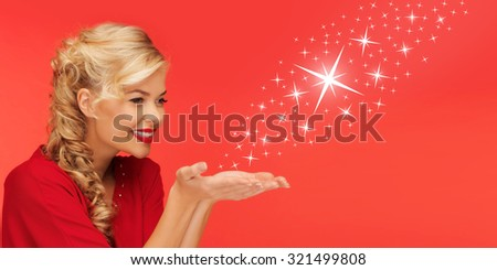 people, holidays, christmas, magic and winter concept - lovely woman in red clothes sending stars from on palms of her hands over red background - stock photo