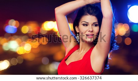 people, holidays, disco, nightlife and leisure concept - beautiful sexy woman in red dress dancing over night street lights background - stock photo