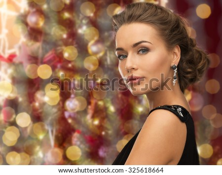 people, holidays, jewelry and glamour concept - beautiful woman wearing earrings over christmas lights background - stock photo