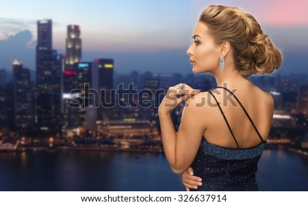people, holidays, jewelry and glamour concept - beautiful woman with diamond earring over night singapore city background - stock photo