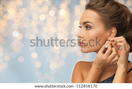 people, holidays, jewelry and luxury concept - close up of woman in evening dress fastening diamond earring over lights background