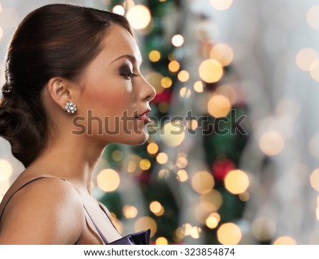 people, holidays, jewelry and luxury concept - woman face with diamond earring over christmas tree lights background - stock photo