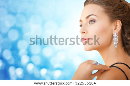 people, holidays, jewelry, luxury and glamour concept - beautiful woman with beautiful diamond earrings over blue lights background - stock photo