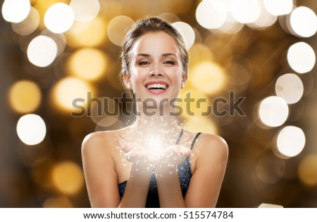people, holidays, magic and luxury concept - happy woman dress with fairy dust on palms
