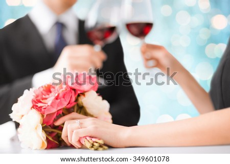 people, holidays, marriage and celebration concept - happy engaged couple with flower clinking wine glasses over blue lights background