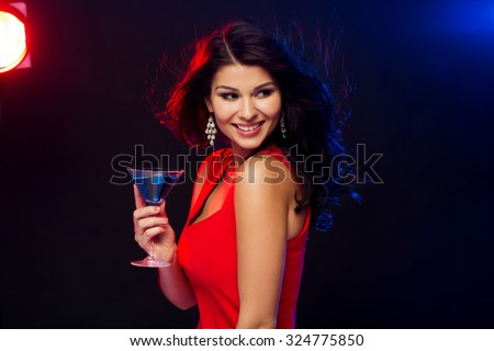 people, holidays, party, alcohol and leisure concept - beautiful sexy woman in red dress with cocktail glass at night club - stock photo