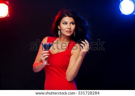 people, holidays, party, alcohol and leisure concept - beautiful sexy woman in red dress with cocktail glass dancing at night club - stock photo