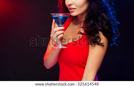 people, holidays, party, alcohol and leisure concept - close up of beautiful sexy woman in red dress drinking cocktail at night club - stock photo