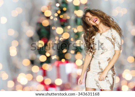 people, holidays, party and fashion concept - happy young woman or teen girl in fancy dress with sequins and long wavy hair dancing over christmas tree lights background - stock photo