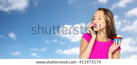 people, holidays, party, junk food and celebration concept - happy young woman in pink dress eating birthday cupcake over blue sky and clouds background - stock photo