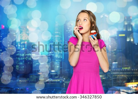 people, holidays, party, junk food and celebration concept - happy young woman or teen girl in pink dress with birthday cupcake over night city and holidays lights background - stock photo