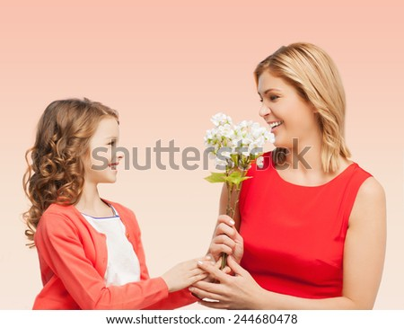people, holidays, relations and family concept - happy little daughter giving flowers to her mother over beige background - stock photo